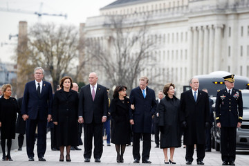 Former President George W. Bush and family members stand just prior to the flag-draped casket of former President George H.W. Bush being carried by a joint services military honor guard from the U.S. Capitol