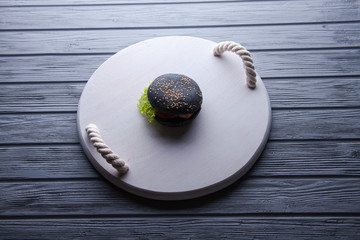 Black wooden serving tray with black burger, potato wedges and ketchup, vertical shot on a grey stone background