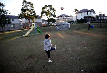 Naohito Hirose kicks a ball to her mother Mariko Hirose at a park in Higashinohara district in Inzai