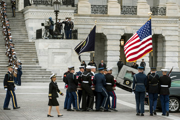 The flag-draped casket of former President George H.W. Bush is transported from the U.S. Capitol to the National Cathedral