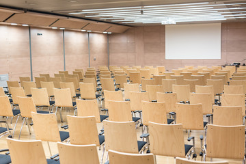 View of empty wooden seats in a modrn lecture hall.