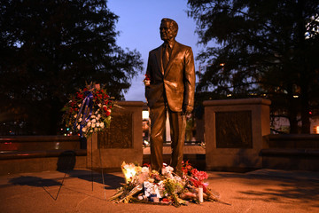 Flowers lay at the base of the George H.W. Bush Monument on the eve of the former presidents funeral in Houston