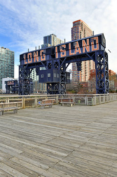 Vintage Railroad Gantries and Long Island sign with skyscrapers and apartment buildings in background, Long Island City, New York