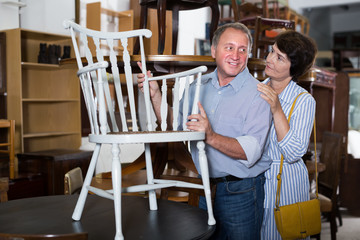 Adult couple are buying vintage style armchair