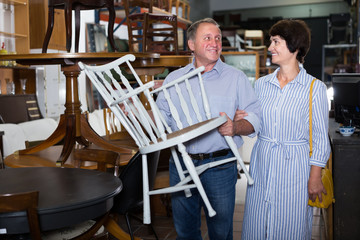 Happy mature couple are buying antique armchair