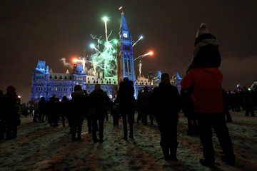 People watch fireworks during the annual Christmas Lights Across Canada ceremony on Parliament Hill in Ottawa