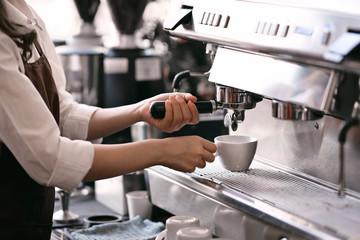 Waitress or Barista using a coffee machine