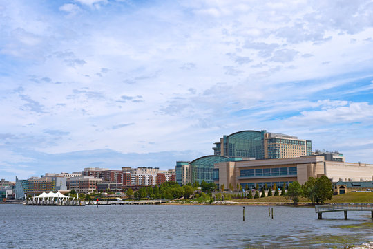 National Harbor waterfront panorama in Oxon Hill, Maryland, USA. Sun shines through cumulus clouds on National Harbor pier and modern buildings along coastline of Potomac River.