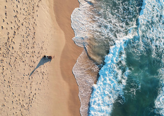 Aerial view of the ocean waves washing on the coast from flying drone Wall mural