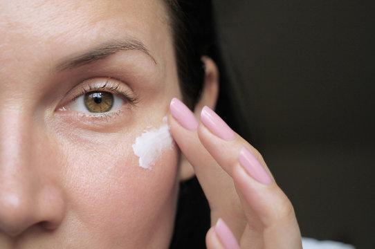 girl applies eye wrinkle cream
