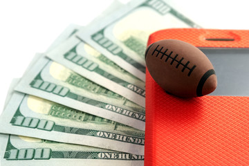 The ball for rugby or American football lies on the screen of the phone in a red case against the background of five hundred US dollars. Concept on the topic of sports betting and bookmaking.