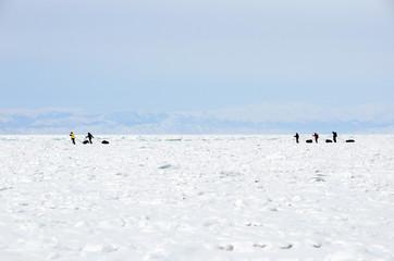 Group of travelers through Ice of Lake Baikal. Cracks, splinters, hummocks