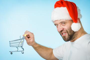 Man in santa hat holds empty shopping cart