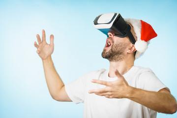Man in virtual reality goggles and santa hat