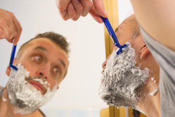 Guy shaving his beard in bathroom