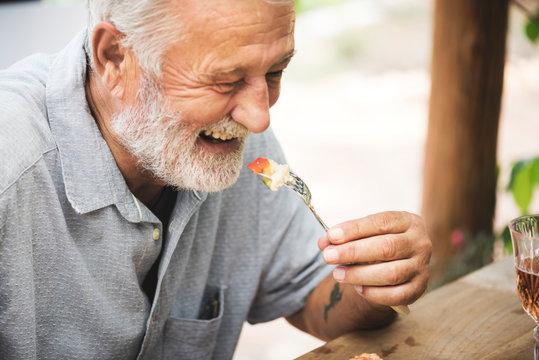 A white haired man enjoying some food