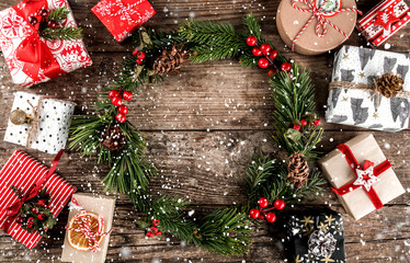 Christmas wreath of Fir branches, many Christmas gift boxes with red decoration and pine cones on wooden background with snowflakes. Xmas and Happy New Year theme. Flat lay, top view