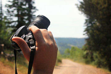 Photographer holding camera and looking down trail