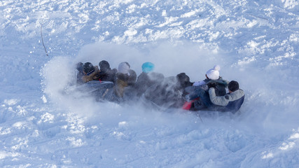 People sledding from the mountain in winter
