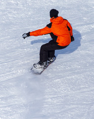 A man snowboarding a mountain in the snow in winter