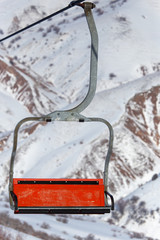 Ski lift and snowboarders in the mountains