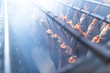 Fish smoked on hooks in smokehouse