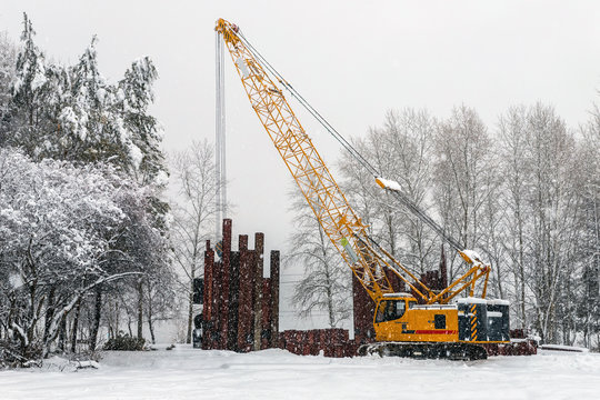 Mobile crane work in a park during snowfall. Work in bad weather conditions.