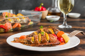 Sea bass stuffed with pieces of fresh lemon and baked with vegetables, bell peppers, carrot and celery. Glass baking form and white plate on wooden rustic table