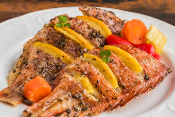 Sea bass stuffed with pieces of fresh lemon and baked with vegetables, bell peppers, carrot and celery. White plate, close-up