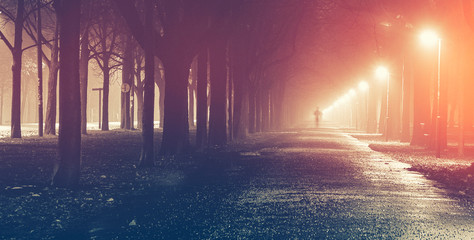 man jogging on the foggy alley at night