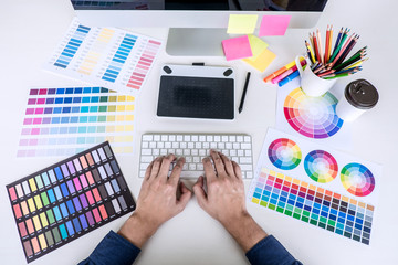 Image of male creative graphic designer working on color selection and drawing on graphics tablet at workplace with work tools and accessories, top view workspace