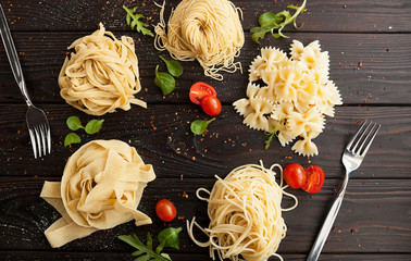 pasta, basil and cherry tomatoes on a wooden table