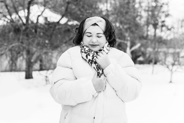 Holidays days, Christmas winter time. Plus size Woman in coat and headband outdoor. Lady in casual clothes, plump lady fashion concept, posing on the street in snowy weather