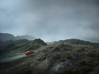 Red sports car drives through mountain landscape