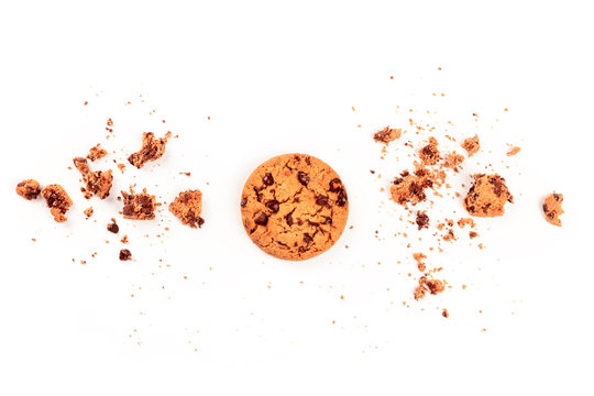 An overhead photo of a freshly baked golden brown chocolate chip cookie, shot from above on a white background with crumbs and copy space