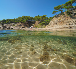 Mediterranean cove in summer with rock and sand underwater, split view half above and below water surface, Cala Estreta, Palamos, Spain, Costa Brava