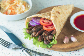 Handmade doner kebab is lying on the white table made of artificial stone Shawarma on the wooden cutting board with chicken meat, onions, salad lies on a dark old wooden table.
