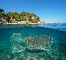 Spain Mediterranean cove with fisherman hut and fish with rock underwater sea, split view half above and below water surface, Cala del Crit, Palamos, Costa Brava