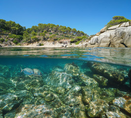 Spain Costa Brava cove with a fisherman hut and fish with rocks underwater, split view half above and below water surface, Mediterranean sea, Cala Cap de Planes, Palamos