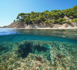 Spain Mediterranean coastline with a beach and underwater an eroded rocky bottom with a fishing net tangled, split view half above and below water surface, Cala Cap de Planes, Palamos, Costa Brava