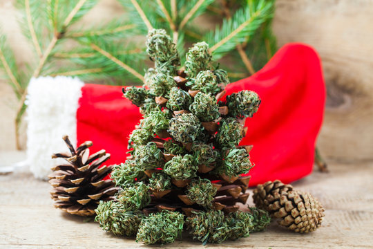 santa red Christmas boot with marijuana on a wooden table on a Christmas New Year's background