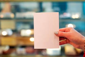 Women holding paper blank, white postcard on christmas background.