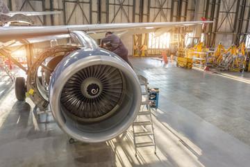 Aircraft engine repair, mechanic installs reverse hoods.