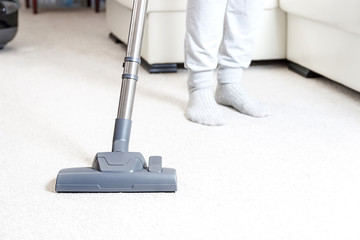 Cleaning the carpet with vacuum cleaner in the living room
