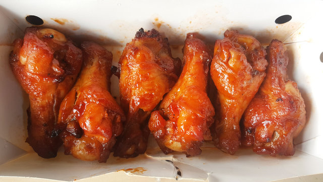Chicken wings in barbecue sauce in delivery box.