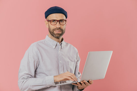 Isolated shot of handsome unshaven male does distance job on portable laptop computer, wears hat and optical glasses, connected to wireless internet, stands over pink background, develops software