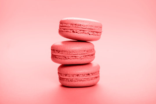 Living coral macaroons on pink background.