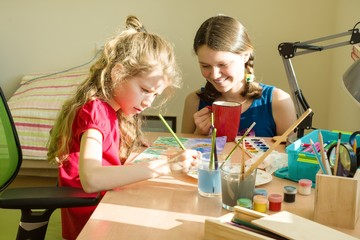 Family, recreation, creativity, home. Girls sisters at home at the table paint with watercolor.