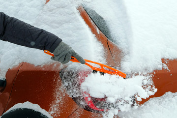 Man clears orange car from snow on a cold winter day after snowfall. Brush in mans hand. Lot of snow on car.