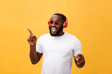 Young African American man wearing headphone and enjoy music over yellow gold Background